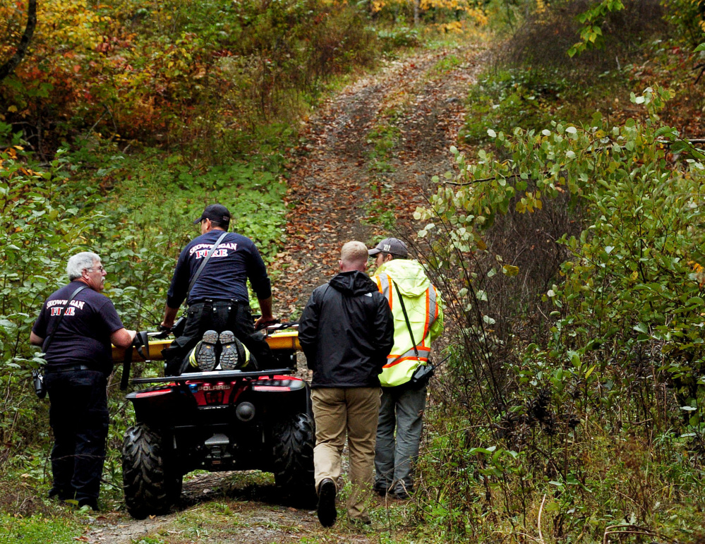 Skowhegan firefighters transport a gurney to the scene where the body was found Sunday off a remote trail in Skowhegan. Authorities on Monday identified the man as Gary Lisherness, 56, of Madison.
