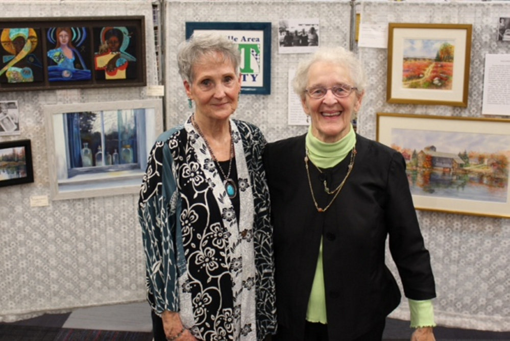 Patricia Binette, left, and Pauline Turner stand in front of a display of their work at an opening reception honoring them at the 30th anniversary of the Waterville Area Art Society they co-founded with Marilyn Dwelley and Peggy Stowers.