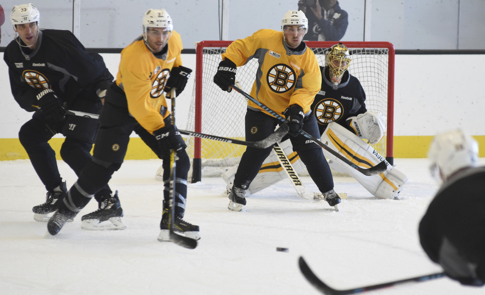 Bruins defenseman Zdeno Chara, left, starts to drop his stick on a shot to goalie Tuukka Rask, right, during practice in Boston on Tuesday. From left are Chara, center Patrice Bergeron, left wing Brad Marchand and Rask.
