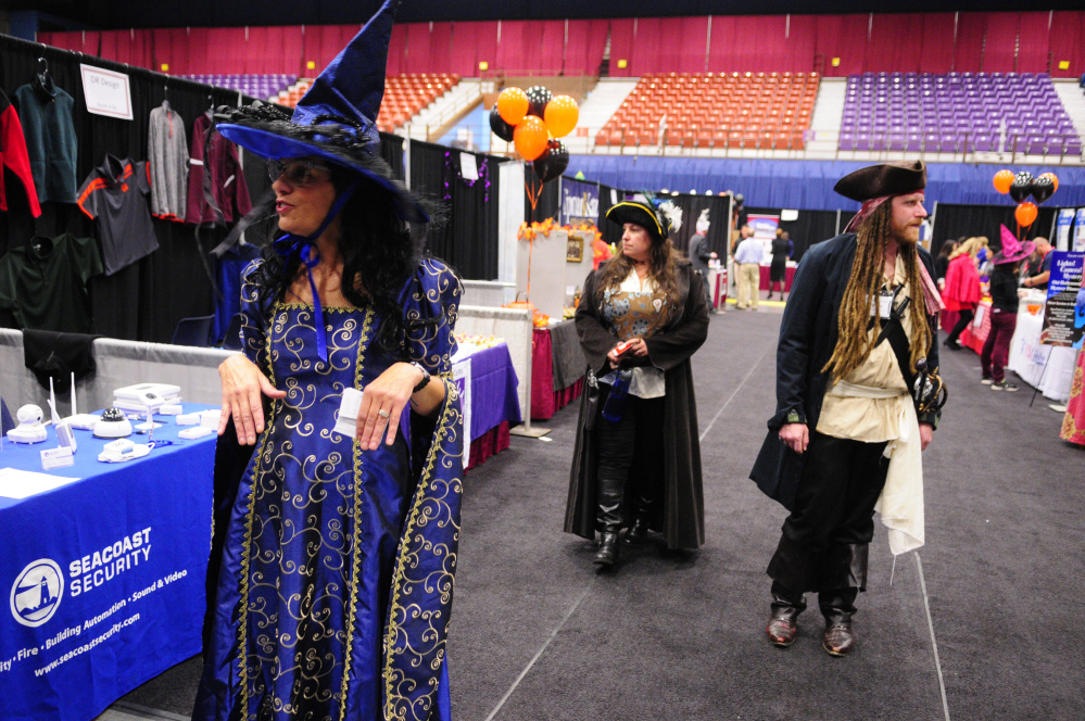 People wearing Halloween costumes while working at Kennebec Valley Chamber of Commercer EXPO booths take a break Wednesday and walk around checking out the rest of the show at Augusta Civic Center.