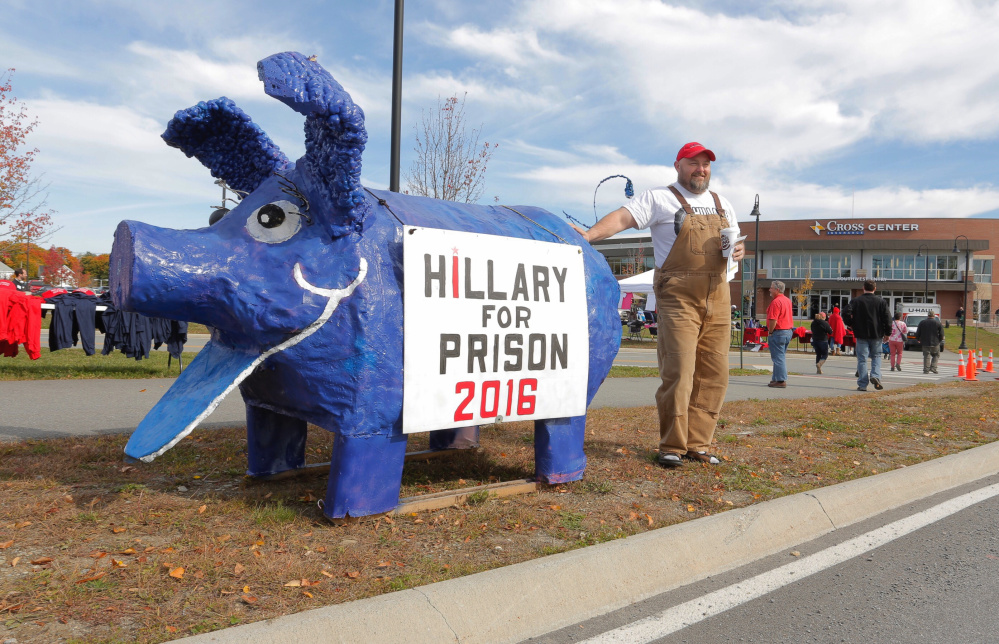 Gary Cromwell of Mercer poses for a photo with a pig sporting a Hillary for Prison 2016 sign outside the Cross Insurance Arena in Bangor on Saturday.