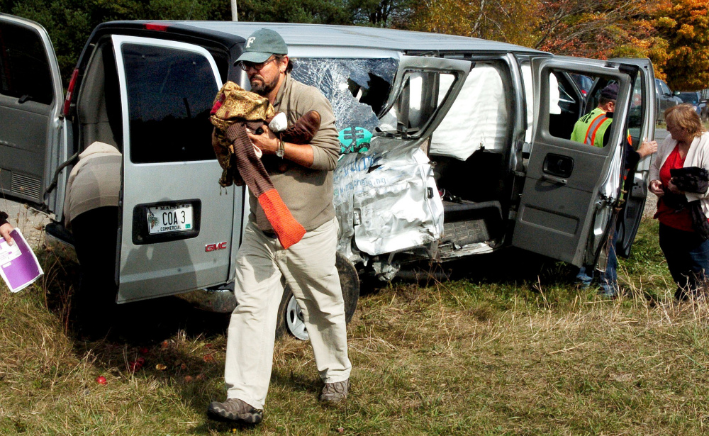College of the Atlantic professor Todd Little-Siebold removes items from the wreckage of a school van that had nine students and staff inside when it collided with another van after turning on to the Crosby Brook Road in Thorndike to attend an event at the Maine Organic Farmers and Gardeners Association on Sunday. Little-Siebold said the students in the school van were shaken up and received relatively minor injuries.