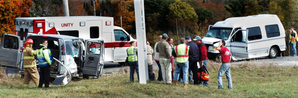 Police and firefighters investigate the scene where two vans collided at the intersection of Route 220 and the Crosby Brook Road in Thorndike on Sunday. Trooper Bethany Robinson said the van at left had nine people from the College of the Atlantic and turned into the path of the van at right.