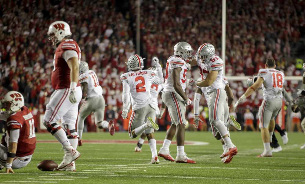 Ohio State players celebrate after defeating Wisconsin 30-23 in overtime Saturday in Madison, Wisconsin.