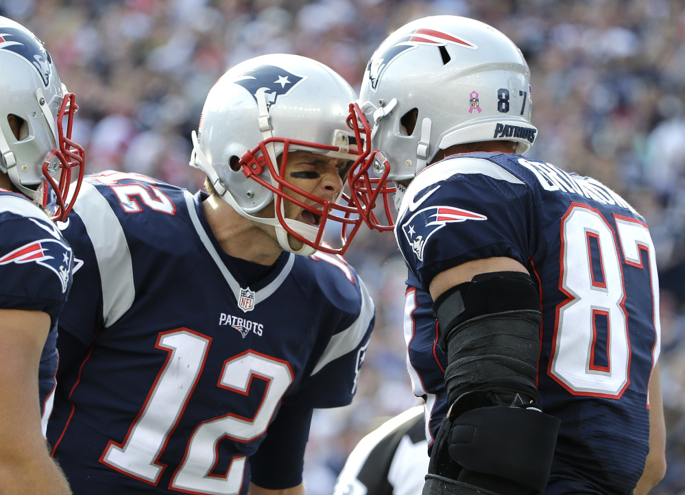 New England Patriots quarterback Tom Brady (12) celebrates his touchdown pass to tight end Rob Gronkowski (87) during the second half against the Cincinnati Bengals on Sunday in Foxborough, Massachusetts.