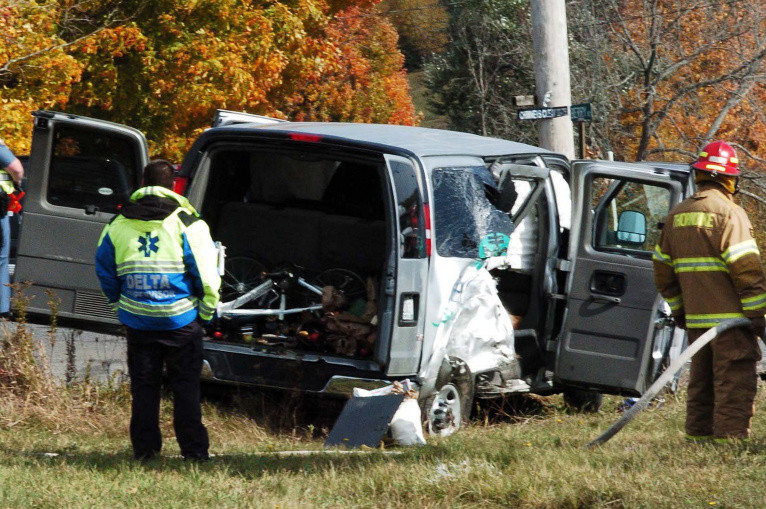 State police and firefighters investigate the scene beside a van filled with nine passengers and operated by the College of the Atlantic after it collided with another vehicle at the intersection of Route 220 and the Crosby Brook Road in Thorndike on Sunday.