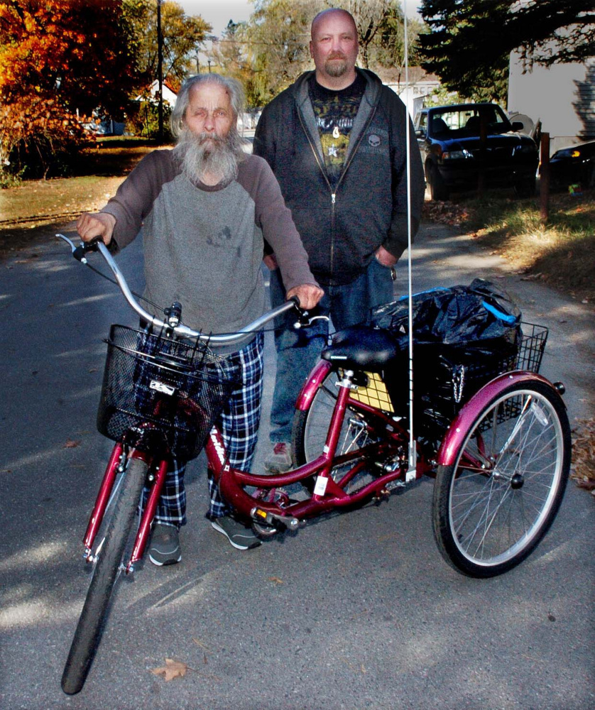 """Neil Woodard, left, known as the """"Bottle Man,"""" stands beside his new tricycle he named Luka on Monday after his other tricycle was damaged and Woodard was injured in a fall. Next to Woodard is Rick Sisco, who spearheaded the effort to raise money for the new tricycle."""
