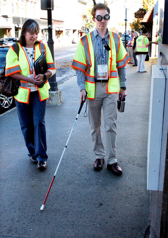 Stacie Beyer watches as Ben Lake navigates sidewalks on Main street in Waterville during a GrowSmart Maine annual conference on Wednesday. Lake was using a walking cane and wore glasses that inhibited vision to illustrate challenges to visually impaired people.