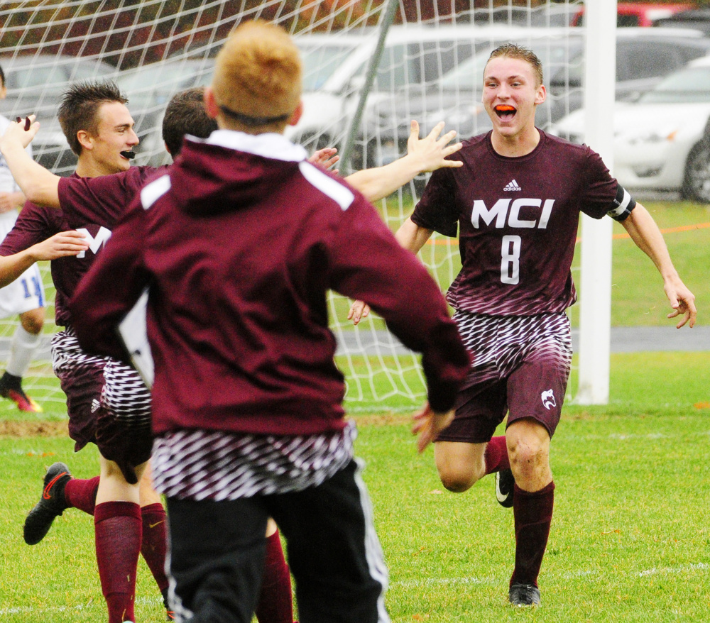Teammates run to celebrate with Devon Varney after he scored the game-winning goal against Erskine in overtime of a Class B North preliminary game Saturday in South China.
