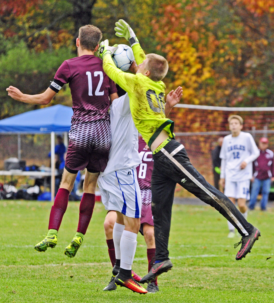 MCI's Carter Richmond and Erskine's Sage Hapgood Belanger, center, and keeper David McGraw jump for a ball in front of the net during a Class B North preliminary game Saturday in South China.
