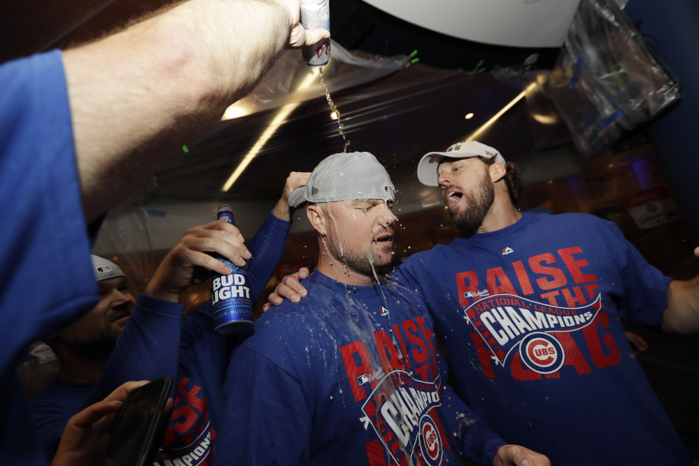 Chicago Cubs' pitchers Jon Lester, left, and John Lackey celebrate after Game 6 of the National League Championship Series against the Los Angeles Dodgers on Saturday in Chicago. The Cubs won 5-0 to win the series and advance to the World Series against the Cleveland Indians.
