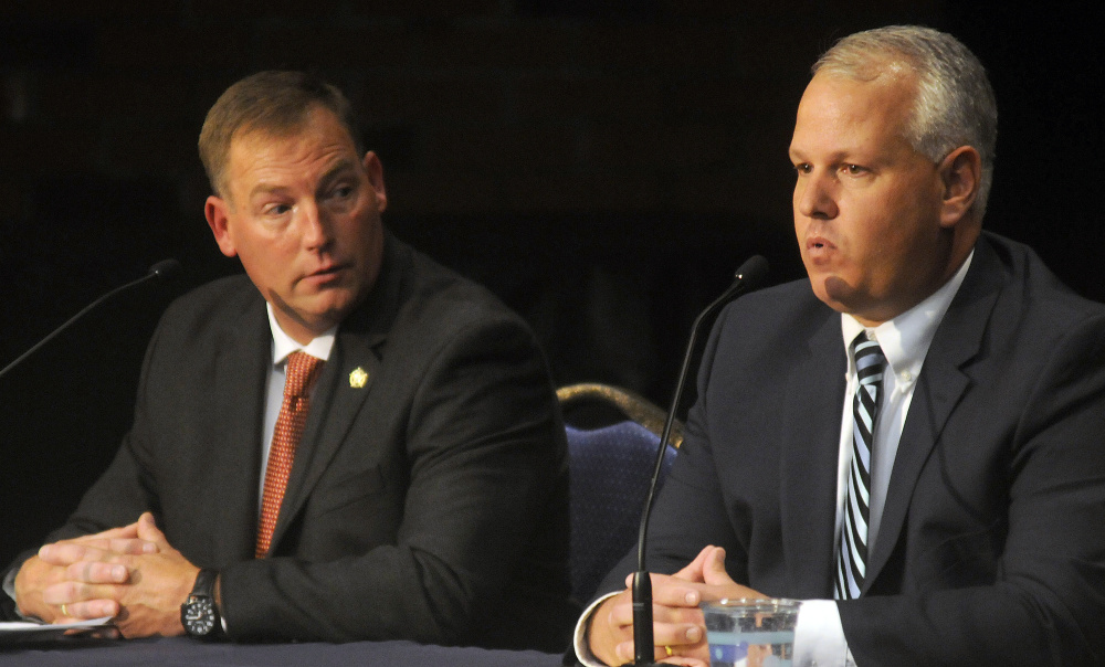 Ken Mason, left, listens to Ryan Reardon respond to a question during the debate for the office of sheriff in Augusta on Monday.