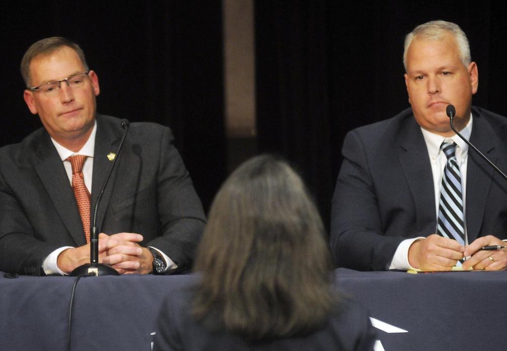 Ken Mason, left, and Ryan Reardon listen Monday to a question from District Attorney Maeghan Maloney during the debate for sheriff held in Augusta.