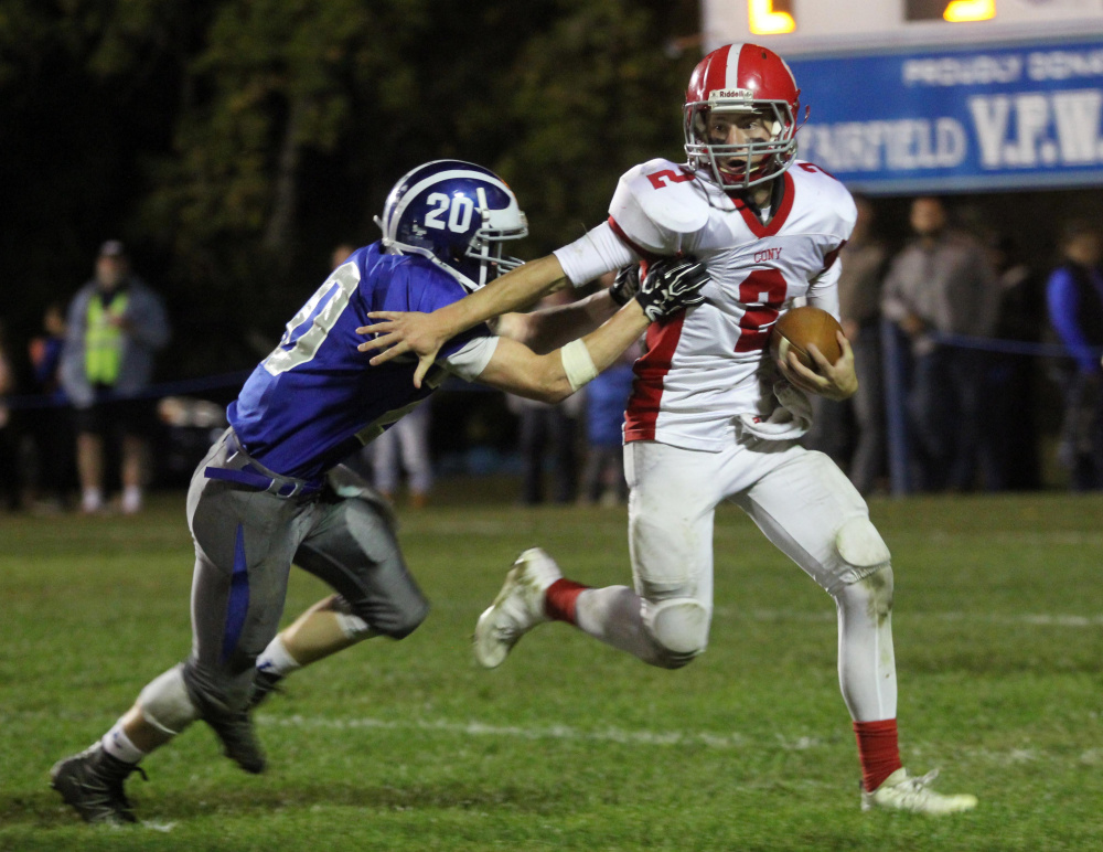 Cony High School quarterback Taylor Heath tries to break a tackle by Lawrence High School's Devon Webb during the first half of a game in Fairfield last month.