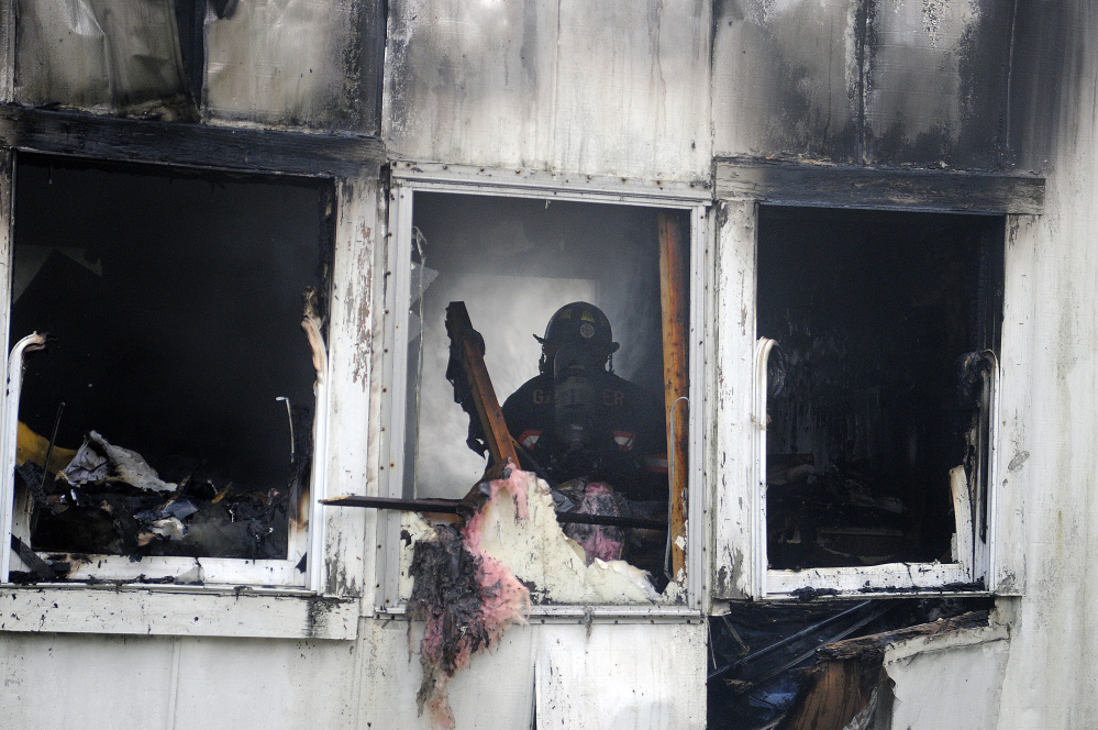 Firefighters extinguish a fire Tuesday inside a home in South Gardiner.