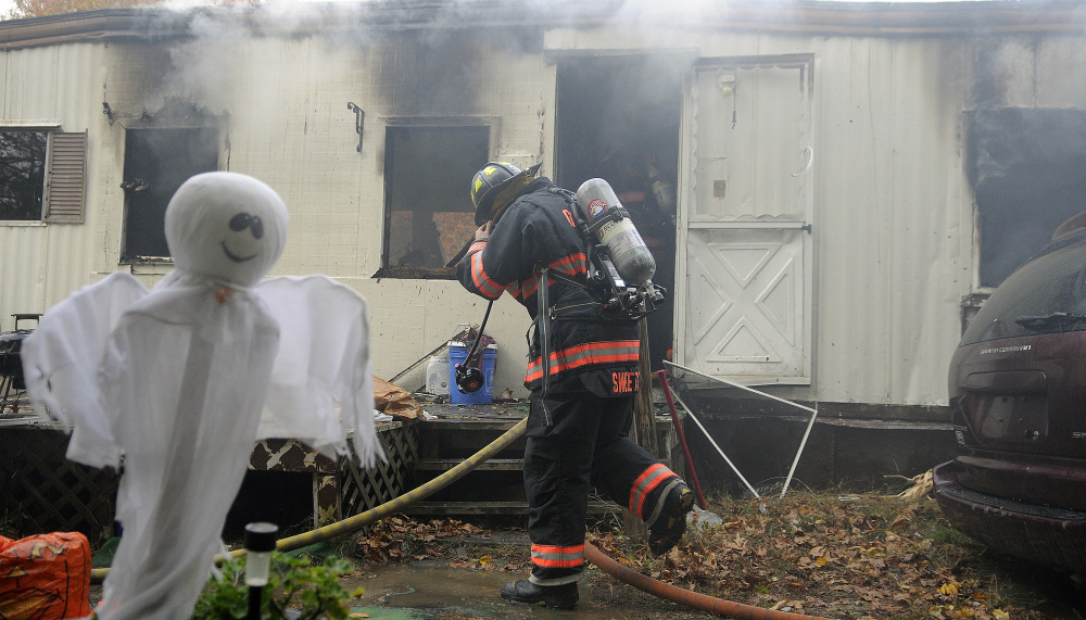 A firefighter enters a home on Leighton Lane in South Gardiner that was destroyed by fire on Tuesday.
