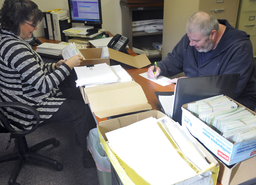 Mark Luken signs a ballot Tuesday before handing it over to West Gardiner Town Clerk Angela Phillis. Phillis said hundreds of ballots have been cast early at the West Gardiner Town Hall.