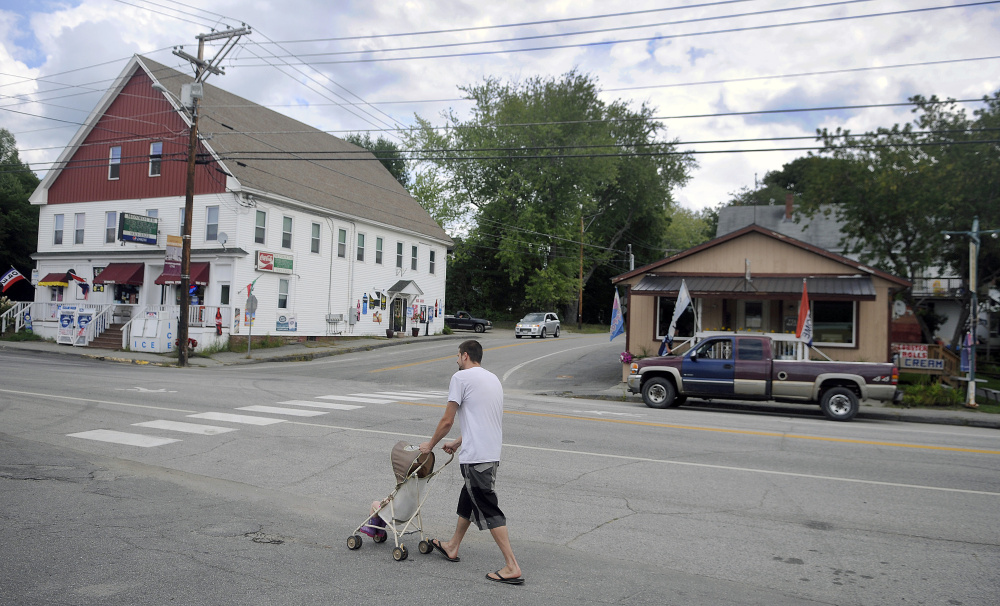 Justin Caouette pushes his daughter, Emily, down Main Street in Monmouth in this September file photo. Monmouth selectmen have approved placing a question on the Nov. 8 ballot asking voters to decide whether to extend a downtown tax increment financing district to include five empty Main Street lots totaling 99 acres.