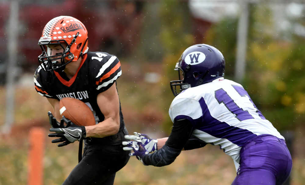 Winslow defender Dylan Hutchinson (14) intercepts a ball intended for Waterville receiver Cooper Hart during a game in Winslow last weekend.