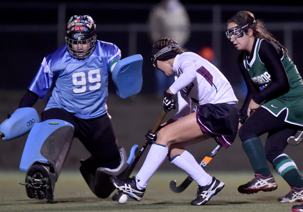 Winthrop goalie Corinna Coulton (99) makes a save on a shot from Maine Central Institute's Madisyn Hartley, center, in the Class C North final Wednesday in Hampden.
