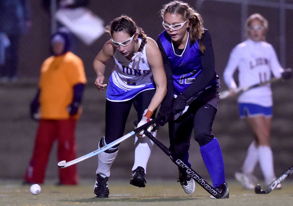 Lawrence's Nora Buck battles for the ball with Belfast's Amy Gaiero during the Class B North final against Belfast on Wednesday night Hampden Academy.