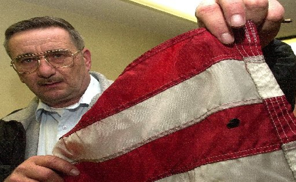 Pittsfield police Chief Steven Emery, shown in 2012, holds an American flag that allegedly was vandalized by a teenager. The flag had been on display outside Reny's department store in Pittsfield. Emery died unexpectedly Saturday after more than 22 years as chief.