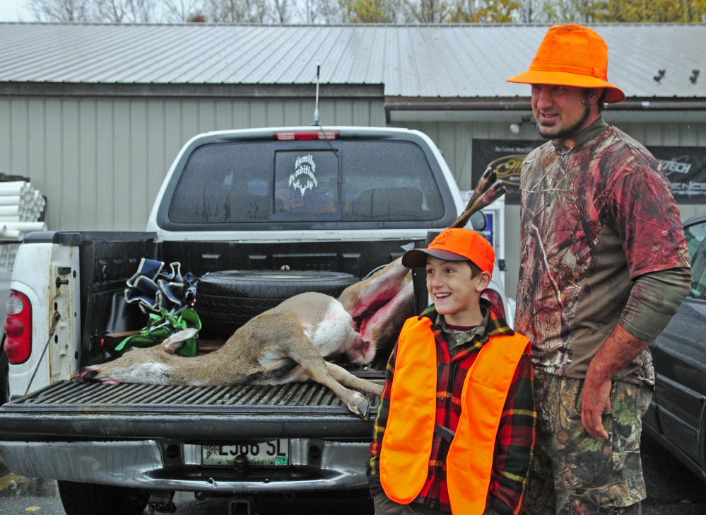Blake Gemelli and his father, Eric Gemelli, talk about the deer that Blake got Saturday, the opening day of firearms season, at Audette's Hardware in Winthrop. The two had been out hunting Oct. 22 on youth day, but Blake didn't get one then.