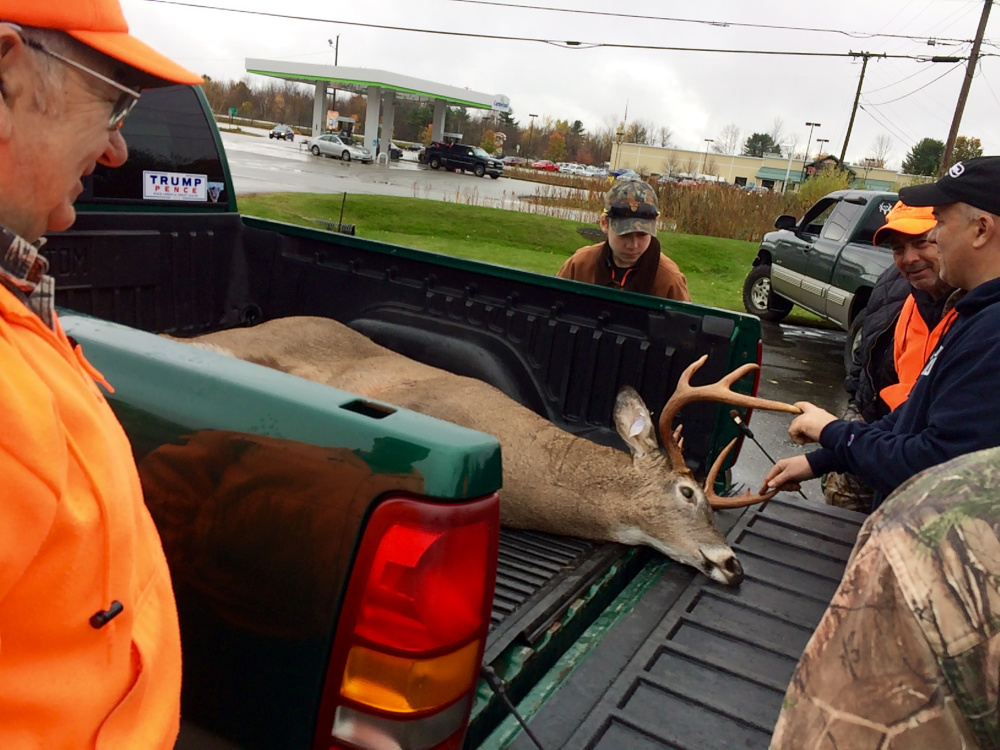Ken Smith, 74, of Winthrop, left, smiles as a small crowd admires the 199-pound, nine-point buck he shot about 2 miles from his house Saturday morning. Saturday was the first day of the regular hunting season for Maine residents.