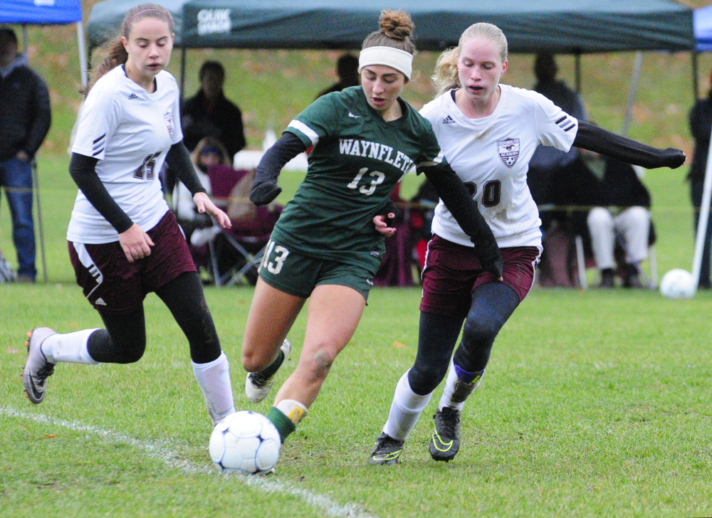 Waynflete's Amelia Bertaska (13) is flanked by Monmouth's Kayla Brooks, left, and Izzy Lewis during a Class C South semifinal game Saturday in Monmouth.