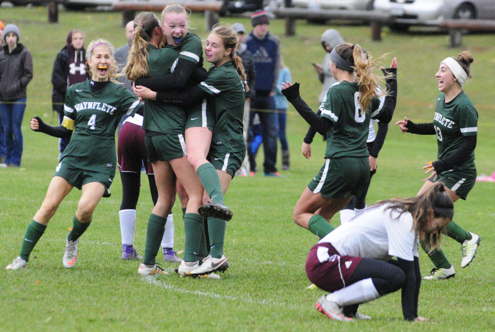 Waynflete teammates mob Lydia Giguere, jumping center, after she scored a goal in overtime to beat Monmouth Academy 2-1 in a Class C South semifinal Saturday in Monmouth.