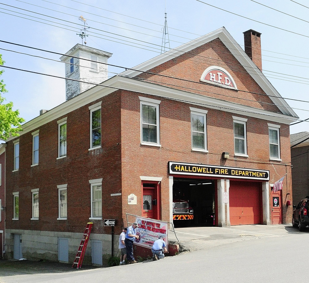 This May 2011 file photo shows Hallowell volunteer firefighters hanging a banner outside the fire station.