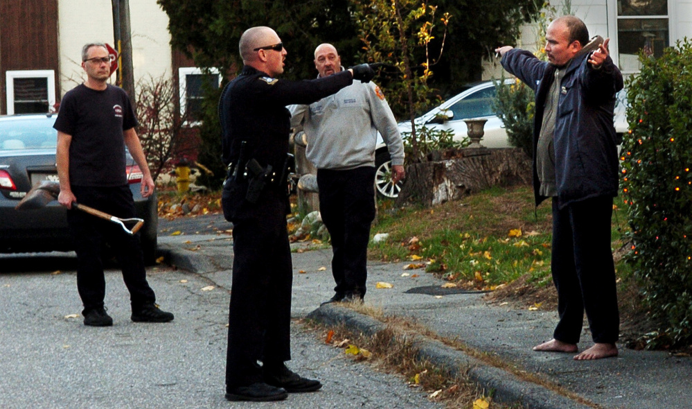 A Waterville police officer orders Daniel Groover, right, to hold up his hands up after confronting the man on Appleton Street in Waterville on Monday. Groover reportedly smashed a rear window in the Waterville Fire Department building and was followed by firefighter Al Nygren, left, with a shovel, and Capt. Rodney Alderman.