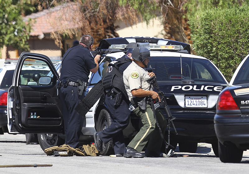 Officers watch a home in Palm Springs, Calif. where two police officers were killed and one wounded.