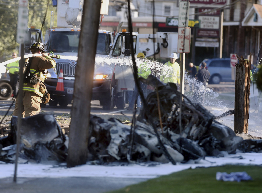 Firefighters extinguish the fire after a plane crashed on Main Street in East Hartford, Conn., on Tuesday.