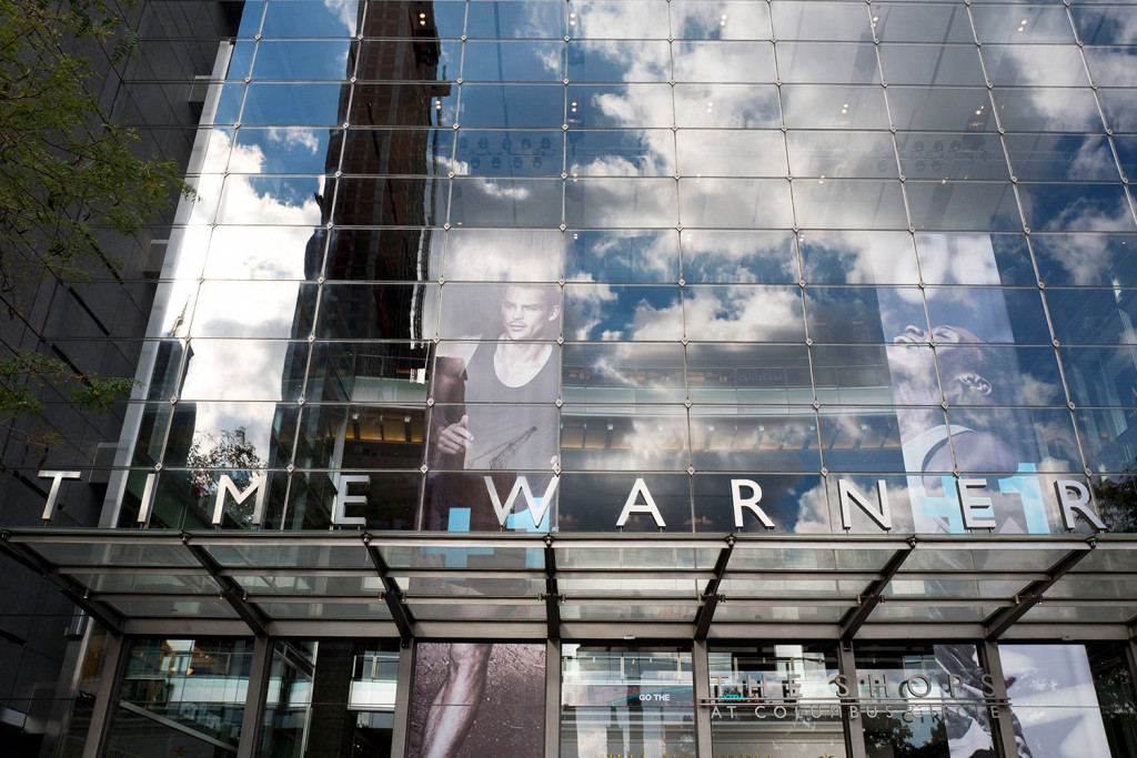 Clouds are reflected in the glass facade of the Time Warner building in New York. AT&T plans to buy Time Warner for $85.4 billion.