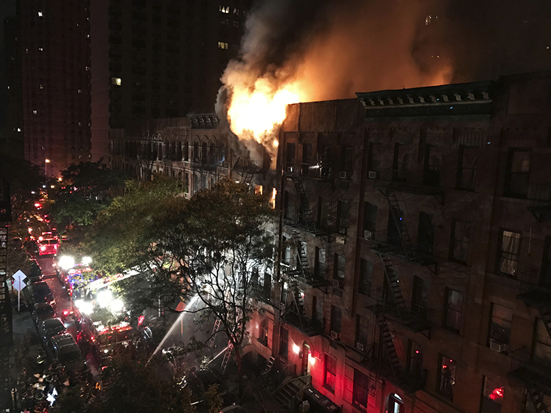 Firefighters work to put out a blaze at an apartment building on the Upper East Side in New York early Thursday.