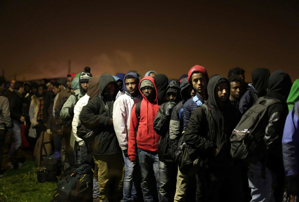 "Migrants line up to register at a processing center in the makeshift migrant camp known as ""The Jungle"" near Calais, northern France, Monday. French authorities say the closure of the slum-like camp will last approximatively a week in what they describe as a ""humanitarian"" operation. <em> Associated Press/Emilio Morenatti</em>"