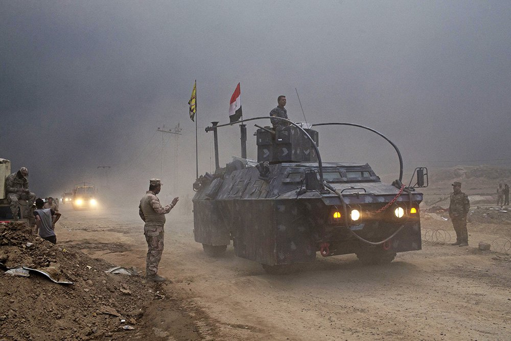 An Iraqi Federal Police vehicle passes through a checkpoint in Qayara, about 30 miles south of Mosul, Iraq, Wednesday, Islamic State militants have been going door to door in farming communities south of Mosul, ordering people at gunpoint to follow them north into the city. <em>Associated Press/Marko Drobnjakovic</em>