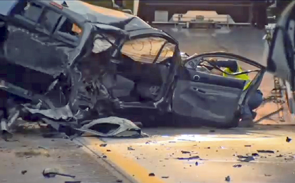 In this still image from video provided by WCAX-TV, a worker attaches a wrecker cable to a vehicle on Interstate 89 early Sunday in Williston, Vt., after a wrong-way driver caused a crash  killing five people, before stealing a police cruiser, striking several vehicles and injuring several people. <em>Via Associated Press</em>