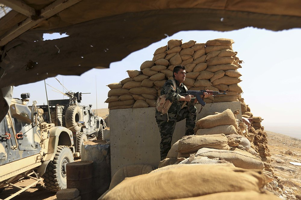An Kurdish Peshmerga fighter stands guard outside Bartella, Iraq, Friday. Bartella is a historically Christian town about 9 miles  from Mosul's outskirts. <em>Associated Press/Khalid Mohammed</em>