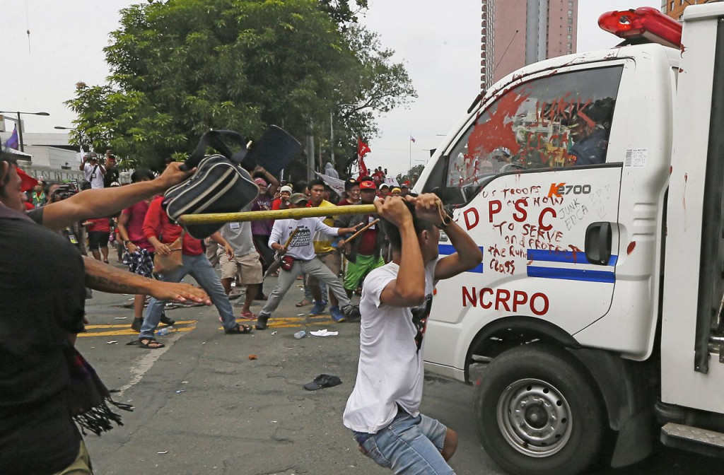 Protesters hit a Philippine National Police van after it rammed into the crowd outside the U.S. Embassy in Manila, injuring an undetermined number of people Wednesday. <em>Associated Press/Bullit Marquez</em>