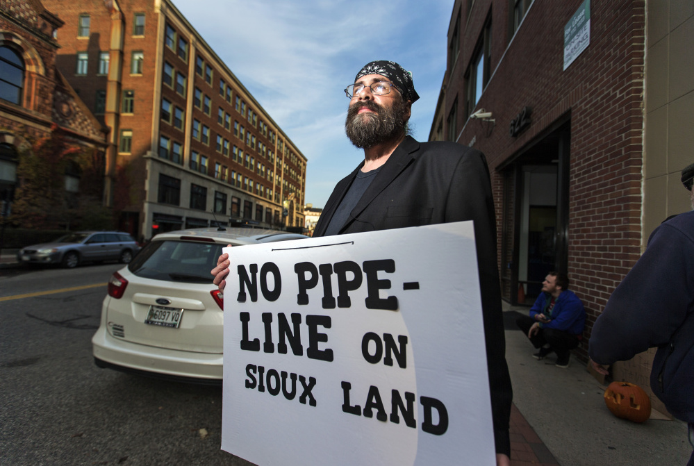 """Chris Thompson of Portland protests outside Hillary Clinton's Portland campaign office Wednesday against the Dakota Access Pipeline. The Democrat's campaign last week issued a statement calling for """"all voices"""" to be heard, but demonstrators want her to take a stronger stand against the situation in the Midwest."""