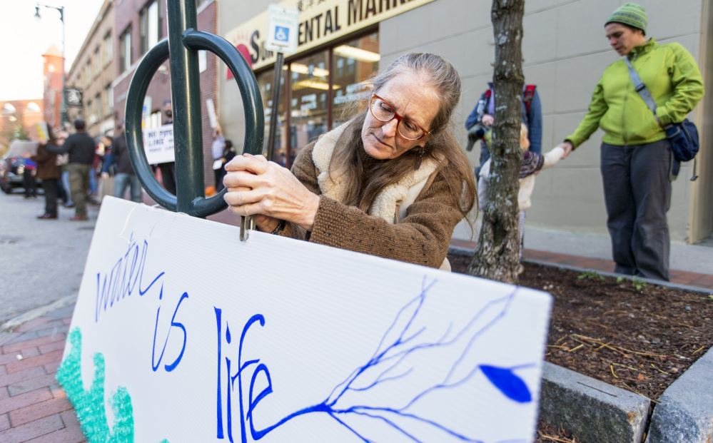 Gina Colombato hangs a sign outside Hillary Clinton's offices in Portland during a protest against the Dakota Access Pipeline.