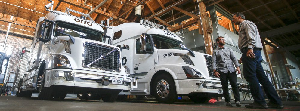 Employees stand next to self-driving, big-rig trucks during a demonstration at the Otto headquarters in San Francisco. Uber's self-driving startup Otto developed technology allowing big rigs to drive themselves. Robots could be coming for a new class of worker: people who drive for a living.