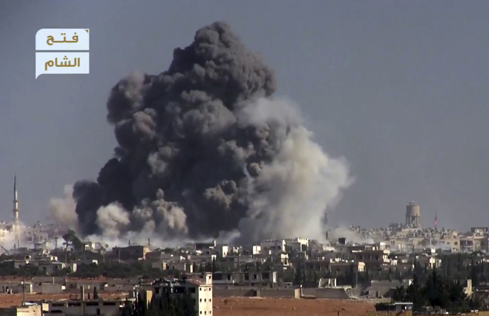 This frame grab from video provided by this militant video by Fatah al-Sham Front that is consistent with independent Associated Press reporting, shows black smoke rising from a suicide bomb attack on Syrian government forces positions in western Aleppo, Syria, Thursday. The Britain-based Syrian Observatory for Human Rights, which monitors the conflict through local contacts, reported that rebels attacked government positions with two explosives-laden vehicles. Syrian rebels launched a fresh wave of attacks on western districts of Aleppo Thursday as airstrikes on a rebel-held village south of the contested city killed civilians, activists said.