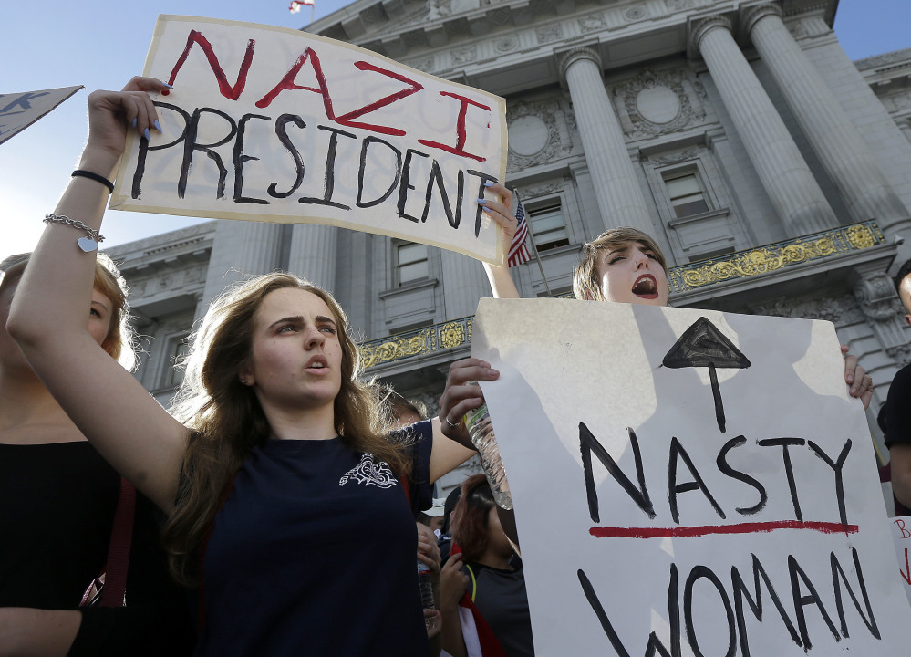 Mission High School students Hope Robertson, left, and Cat Larson yell as they protest with other high school students in front of City Hall in San Francisco on Thursday. They are opposed to Donald Trump's presidential election victory.