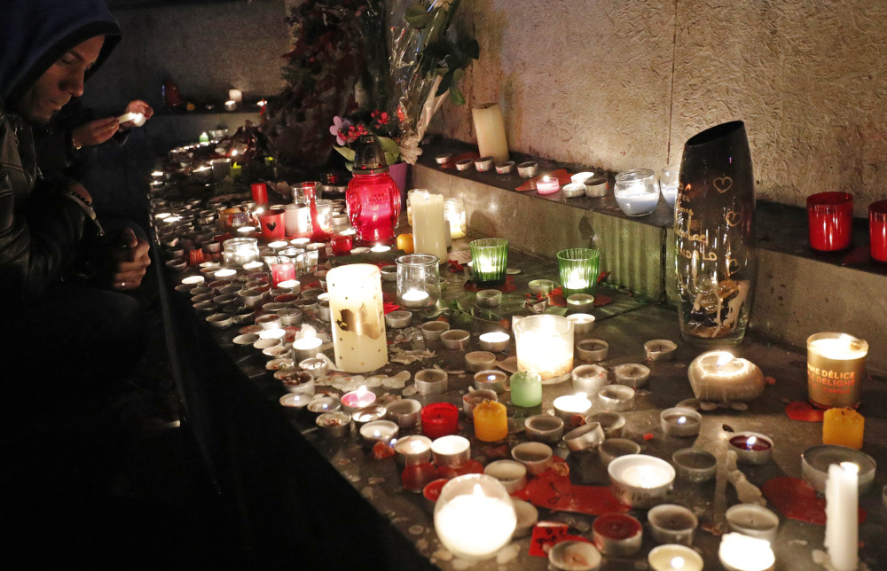 A man pays his respects Sunday at the Place de la Republique in Paris, France, after ceremonies honoring the victims of last year's Paris attacks that targeted the Bataclan concert hall and other sites.