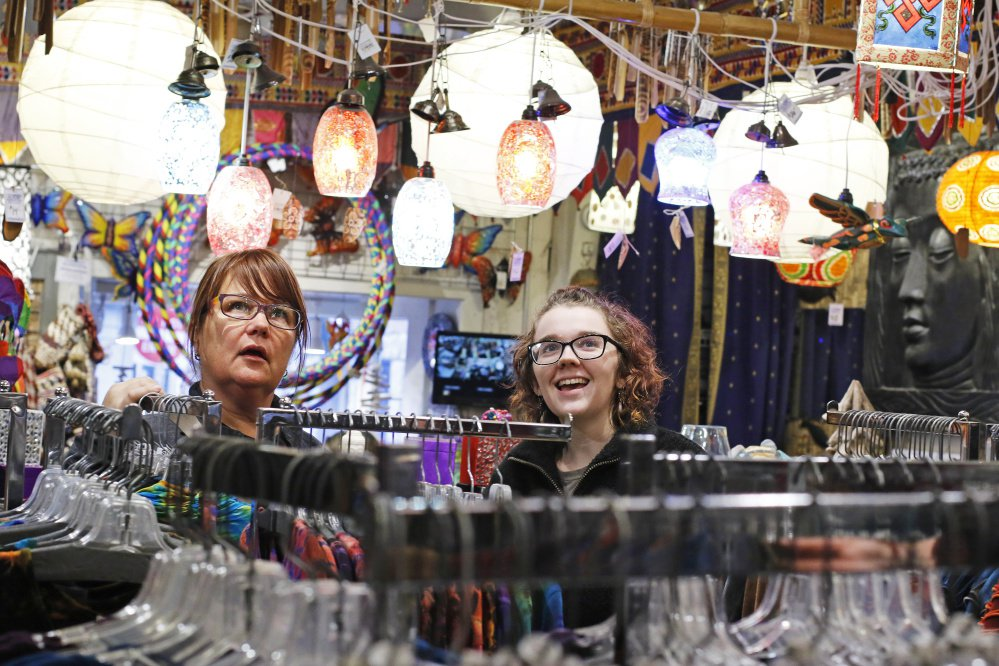 Rae Jett, right, a year-round worker at Mexicali Blues, helps a customer pick out a tea light Friday. To try to attract seasonal workers, the retailer has raised the hourly pay to $11.