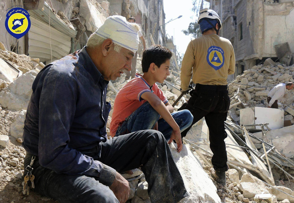 Residents sit in rubble in rebel-held eastern Aleppo, where Syrian activists say bombing has resumed.