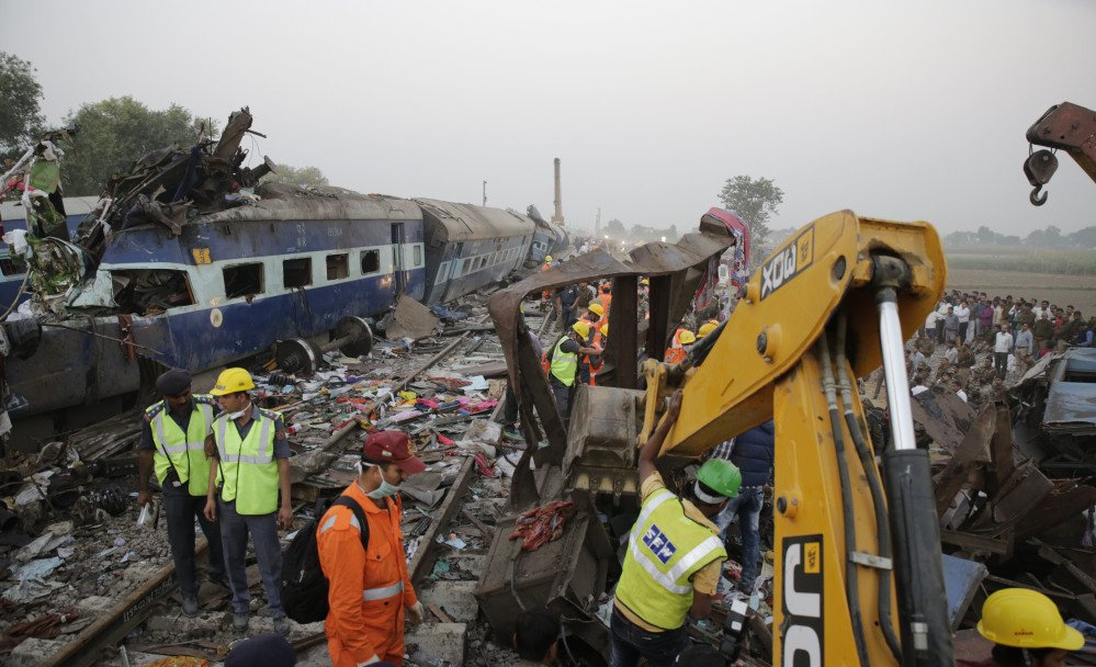 Rescuers use machinery to remove debris Sunday after 14 coaches of an overnight passenger train derailed near a village in northern India. The cause was not immediately clear. Accidents are relatively common on India's sprawling rail network.